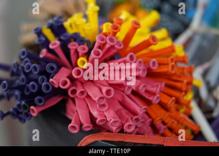 bright colourful deflated long balloons - Stock Image