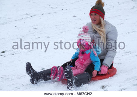 Nottingham, England, 1 March 2018 Mother qand young daughter sledging in front of Wollaton Hall in snow from 'The - Stock Image