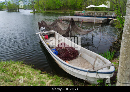 Small fishing boat with nets on the shore of lake Onuma, Hokkaido, Japan. - Stock Image