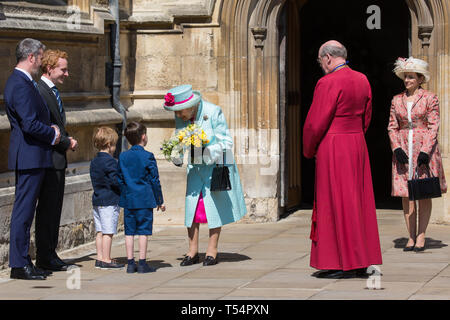 Windsor, UK. 21st April 2019. The Queen is presented with a traditional posy of flowers by two young boys as she leaves St George's Chapel in Windsor Castle with the Dean of Windsor, the Rt Revd David Conner KCVO, after attending the Easter Sunday service. Credit: Mark Kerrison/Alamy Live News - Stock Image
