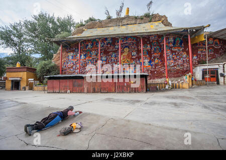 Tibetan Buddhist pilgrim performing full body prostrations in front of thousand Buddha cliffside sculpture in Lhasa, - Stock Image