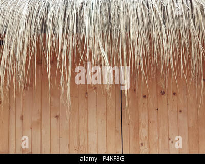 Reed decoration of a wooden pine boards facade of a vacation building. - Stock Image