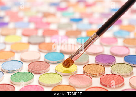 Cosmetic brushes over large colored eye shadows bundle. Selective focus on the brushe - Stock Image