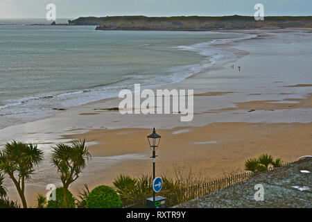 Dog walkers enjoying the almost deserted South Beach in Tenby, in Winter. View overlooking beach from cliff top.Tenby, S.Wales UK - Stock Image