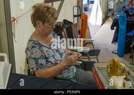 Lady display minder crocheting to pass the time at Wings and Wheels - Stock Image
