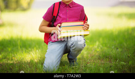 Child with rucksack sitting in the park near school - Stock Image