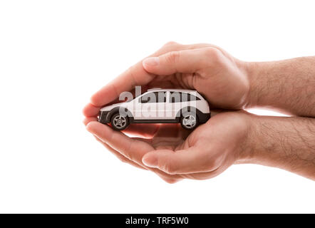 Car protection. Small white car covered by hands isolated on white background with clipping path - Stock Image