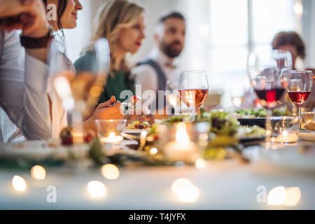 A happy big family sitting at a table on a indoor birthday party, eating. - Stock Image