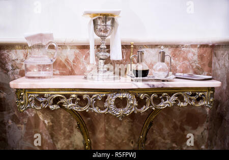 Catholic liturgical objects displayed over marble table at church. Chalice, wine and water pitcher, bell - Stock Image