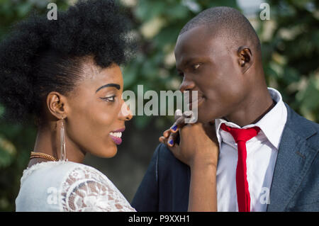 Close-up of young couple in love face to face outside and looking at each other in the eyes smiling - Stock Image