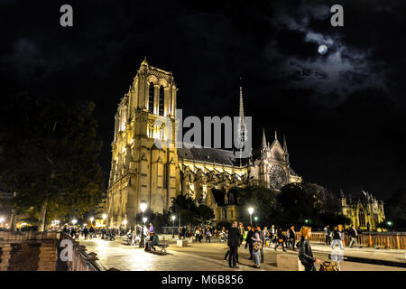 Late night view of Notre Dame Cathedral taken from the Pont au Double bridge on the Ile de la Cite under a full - Stock Image
