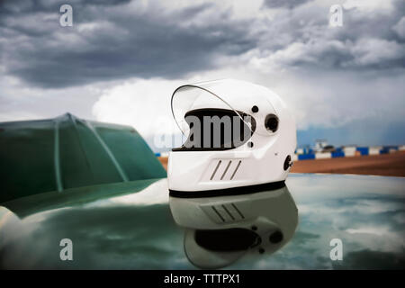 Close-up of white helmet on car hood against cloudy sky - Stock Image