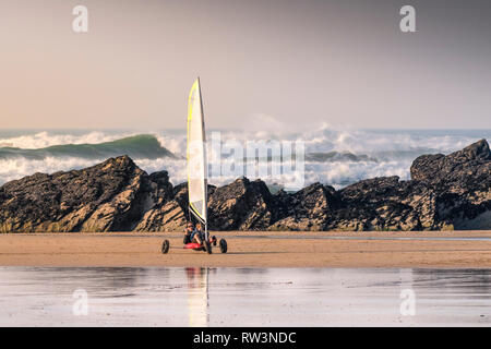 A father and his son having fun with a Ludic Seagull sand yacht on Fistral Beach in Newquay Cornwall. - Stock Image