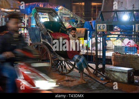Horizontal portrait a pulled rickshaw owner waiting for business in Kolkata aka Calcutta, India. - Stock Image