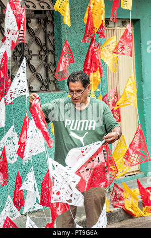 A Mexican man works to untangle papel picado banners in preparation for the 8th Night Celebration marking the end of the Feast of St Michael in the central Mexican town of Uriangato, Guanajuato. Every year the town decorates 5km of road with religious icons in preparation for the statue of the patron saint to be paraded through the town. Uriangato became an international sensation after wowing Brussels with their floral carpet displayed at the Brussels Grand-Place during the Belgium Floral Carpet festival. - Stock Image