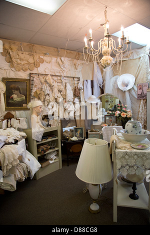 Room in antique shop displaying lace, vintage and antique furniture, books etc.. - Stock Image