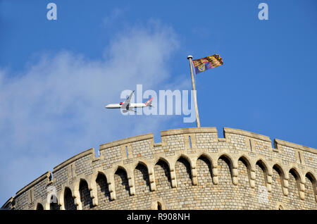 An aeroplane out of London Heathrow airport passes over the Keep of Windsor Castle, with the Royal Standard flying. - Stock Image
