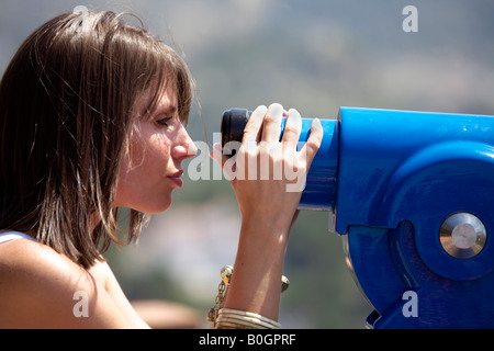 Young woman tourist looking though telescope at a viewpoint in Mijas Pueblo, Costa del Sol, Andalucia, Spain - Stock Image