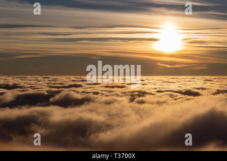 Beautiful sunset over a valley filled by fog - Stock Image
