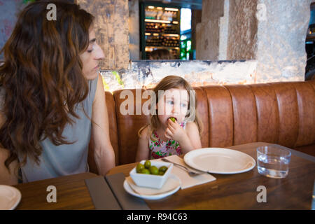 Four years age blonde girl next to woman mother sitting in brown leather sofa at restaurant eating olive with hand - Stock Image