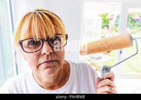 Decorator, decorating, woman decoration, covered in paint, using paint roller, paint roller, paint splatter, female decorator, woman decorator, paint - Stock Image