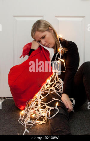 A woman has fallen asleep next to a bundle of christmas lights and a red santa sack - Stock Image