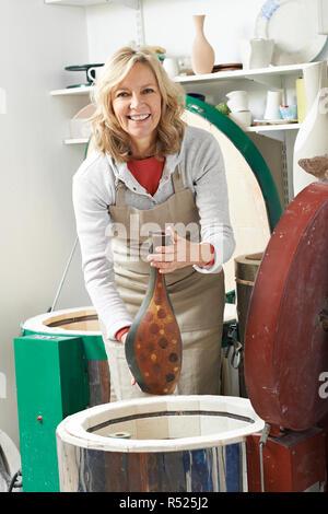 Portrait Of Mature Woman In Pottery Studio Firing Vase In Kiln - Stock Image