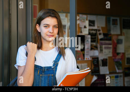 Portrait of a beautiful student girl at the school entrance with bulletin board at the background - Stock Image