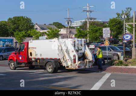 A Tisbury Department of Public Works sanitation crew collects garbage on Water Street in Vineyard Haven (Tisbury), Massachusetts on Martha's Vineyard. - Stock Image