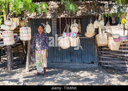 Dili, Timor-Leste - Aug 11, 2015: Local elderly native East Timorese woman, street vending traditional wicker baskets hanging on ropes, at a tin hut u - Stock Image