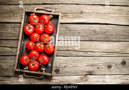 Fresh tomatoes in a wooden tray. On a wooden background. - Stock Image