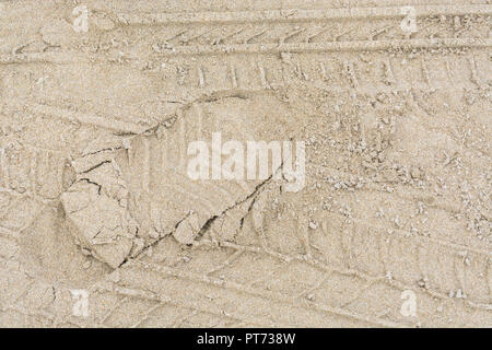 Tyre tracks and footprint in sand. - Stock Image