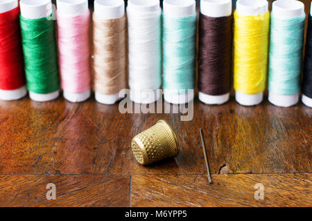 Thimble and a needle on an antique wood veneer full of cracks and scratches. Closeup. Spools of colored threads - Stock Image