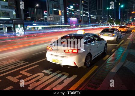 SEOUL, SOUTH KOREA - APRIL 16, 2019 : Neons, lights and Taxis waiting for customers, night urban scene on Gangnam Daero Avenue. - Stock Image