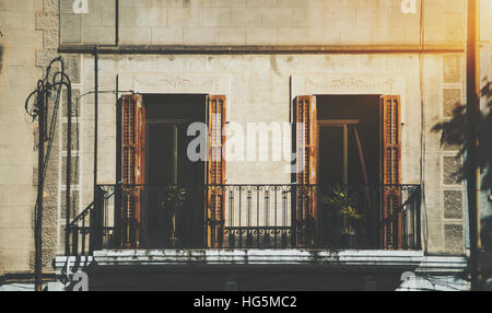 Close-up view of facade with balcony and two windows with opened blind, and plants inside old house in touristic - Stock Image
