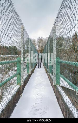 A man is walking on the dam in Lac de Faux near Faux-la-Montagne, Creuse, Nouvelle-Aquitaine - Stock Image