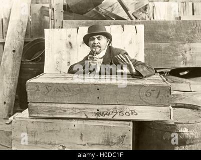 Cornered man behind wooden crates pointing gun - Stock Image