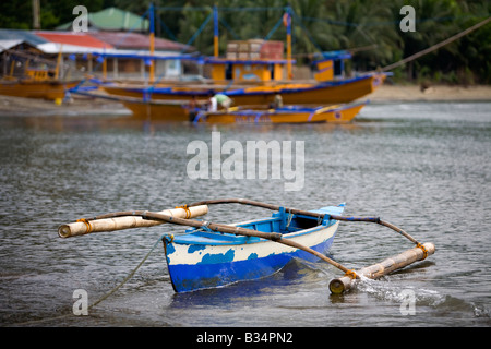 A small weathered bangka boat tied to the beach in Mansalay, Oriental Mindoro, Philippines. - Stock Image