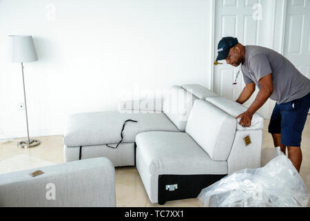 Miami Beach Florida North Beach West Elm furniture delivery Black man unpacking assembling putting together sofa - Stock Image