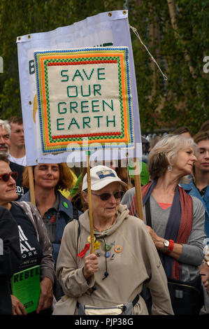 London, UK. 8th September 2018. A woman holds a hand-embroidered placard at the Climate Reality rally in front of Tate Modern, one of thousands around the world demanding urgent action by government leaders to leaders commit to a fossil free world that works for all of us.  community leaders, organisers, scientists, story Credit: Peter Marshall/Alamy Live News - Stock Image