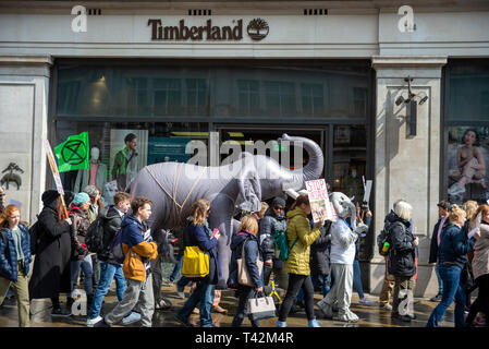 Protesters carry an inflatable elephant through streets of london at a stop trophy hunting and ivory trade protest rally, London, UK passing Timberland shop store - Stock Image