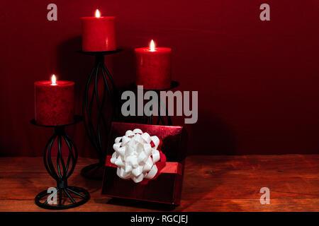 Three red candles in metal holders and red rose, present with white bow on wooden table. - Stock Image