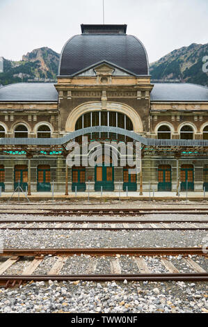 Entrance front view of the abandoned Canfranc International railway station and its railway tracks (Canfranc, Pyrenees, Huesca, Aragon, Spain) - Stock Image