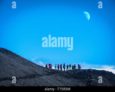Back view of professional mountaineers in warm clothes walking on icy surface glacier by snowy mountain in Iceland - Stock Image