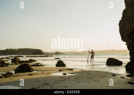 Mature man standing at waters edge holding surf board - Stock Image