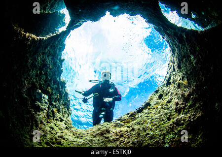 a young female diver near the surface and posing underwater framed in a limestome rock circle against a light blue - Stock Image