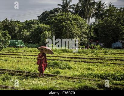 Buddhist monk seen from a train window, Myanmar. - Stock Image