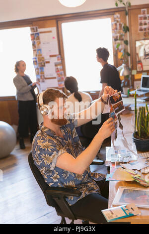 Creative male designer with headphones reviewing photograph proofs in office - Stock Image