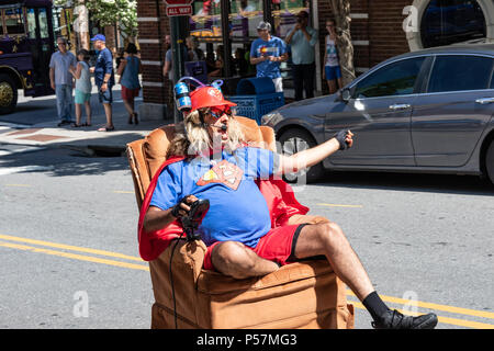 ASHEVILLE, NC, USA-13 MAY 18: Curious character in a motorized recliner chair on the street in downtown Asheville, saying unintelligible things throug - Stock Image