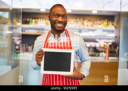 African waiter holds empty signboard in front of bar or restaurant - Stock Image